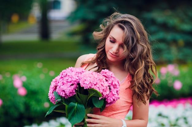 Romantische vrouw met bloemen in hun handen Premium Foto