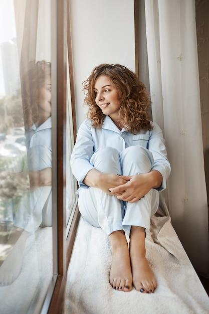 Romantische ziel die droomt van het vinden van een gepassioneerde soulmate. portret van aantrekkelijke gezellige europese meisjeszitting op vensterbank in nachtkleding, kijkend door venster met glimlach, denkend of hebbend idee Gratis Foto