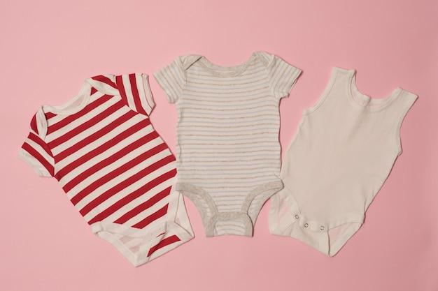 Romper drie op een roze achtergrond. kleding concept Premium Foto