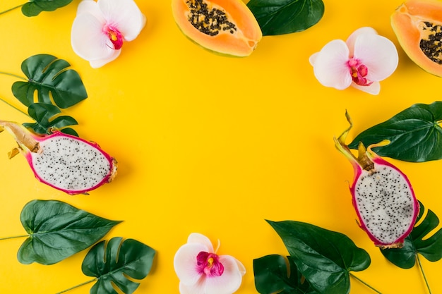 Rond frame gemaakt met kunstmatige bladeren; orchidee; papaja en dragon fruit op gele achtergrond Gratis Foto