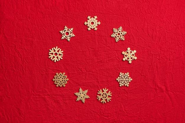 Rond kader van houten sneeuwvlokken op een rode achtergrond. kerstmis nul afvalconcept. plat lag, bovenaanzicht. Premium Foto