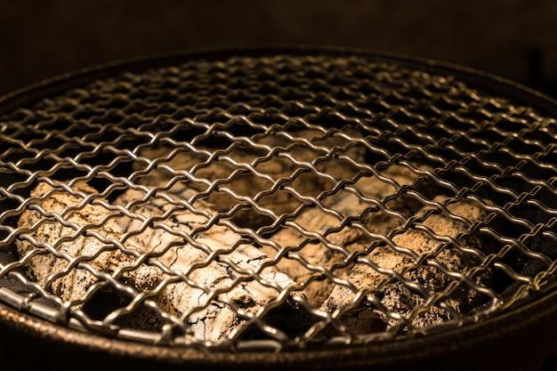 Rond metalen rooster op de houtskoolkachel. Premium Foto