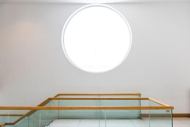Rond venster op een witte muur Gratis Foto