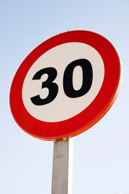 Ronde 30 snelheidsbeperkingsteken tegen blauwe hemel Gratis Foto