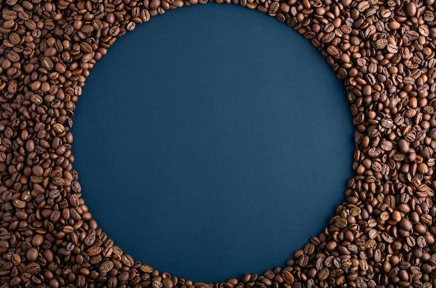 Ronde frame gemaakt van koffie bonen op zwarte achtergrond. gorizontale opstelling. bovenaanzicht. ruimte voor tekst kopiëren. Premium Foto