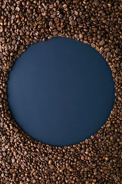 Ronde frame gemaakt van koffie bonen op zwarte achtergrond. verticale opstelling. bovenaanzicht. ruimte voor tekst kopiëren. Premium Foto