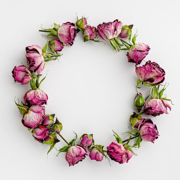Ronde frame of krans gemaakt van gedroogde roze rozen op wit. creatieve sjabloon en vakantie achtergrond. Premium Foto