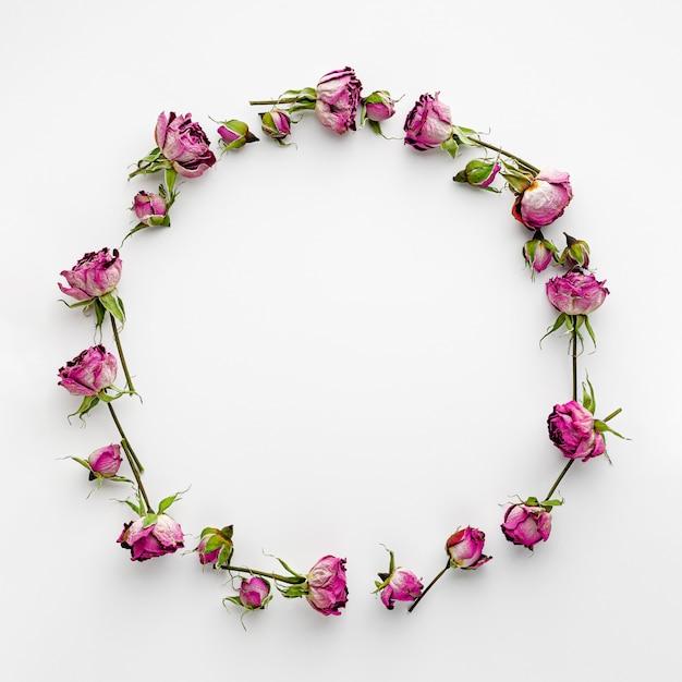 Ronde frame of krans gemaakt van gedroogde roze rozen op wit Premium Foto