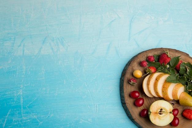Ronde fruitschaal met peren, appel en bessen in de hoek Gratis Foto