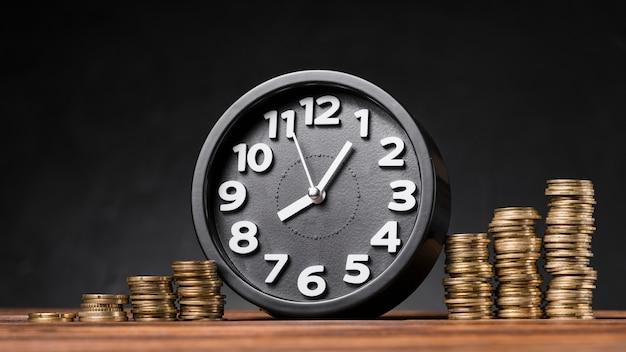 Ronde klok tussen de toenemende munten op houten bureau tegen zwarte achtergrond Gratis Foto