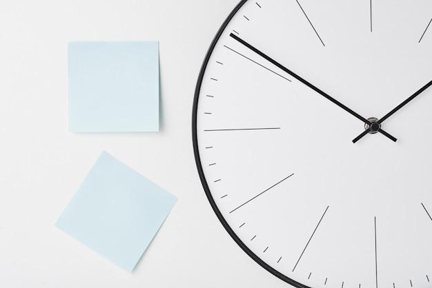 Ronde muurklok en blauwe stickers op wit Premium Foto
