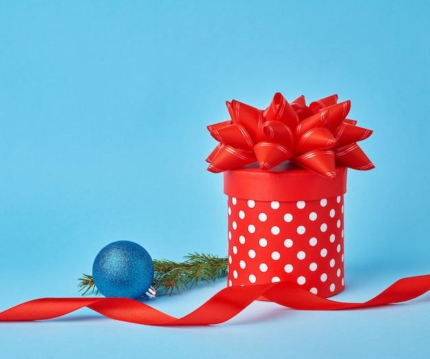 Ronde rode kartonnen doos in witte stippen met een strik, takje sparren met een glanzende blauwe bal Premium Foto