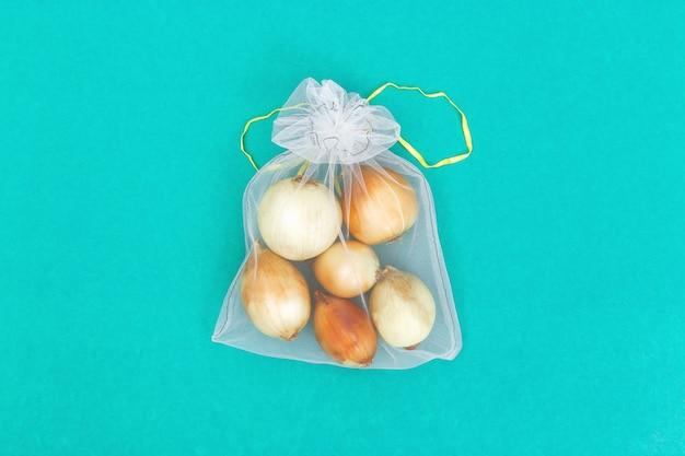 Ronde uien in herbruikbare eco-zakjes. verse groenten in zakken van transparant textiel voor opslag van voedsel. plastic vrij concept. plat liggen. bovenaanzicht. Premium Foto