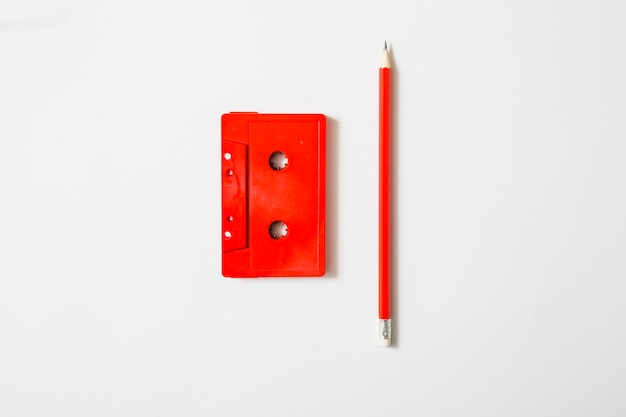 Rood cassettebandje en potlood op witte achtergrond Gratis Foto