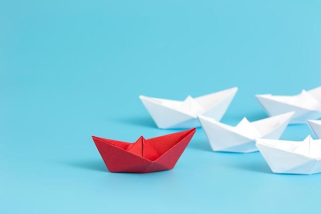 Rood document schip dat onder wit op blauwe achtergrond met exemplaarruimte leidt. Premium Foto