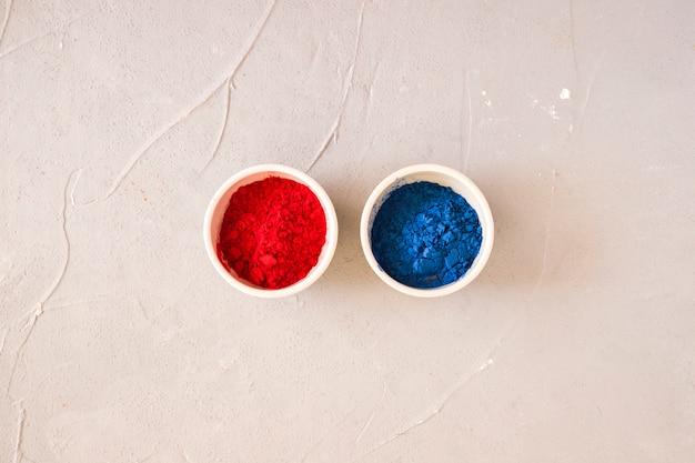 Rood en blauw holi gekleurd poeder in de witte kom op achtergrond Gratis Foto