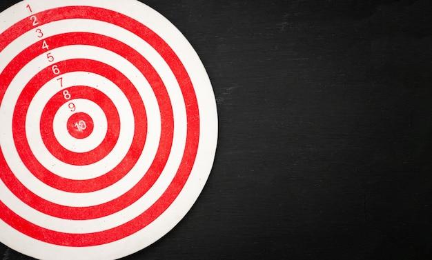Rood en wit dartbord dat met rimpels op een zwarte houten achtergrond wordt gevuld. Premium Foto