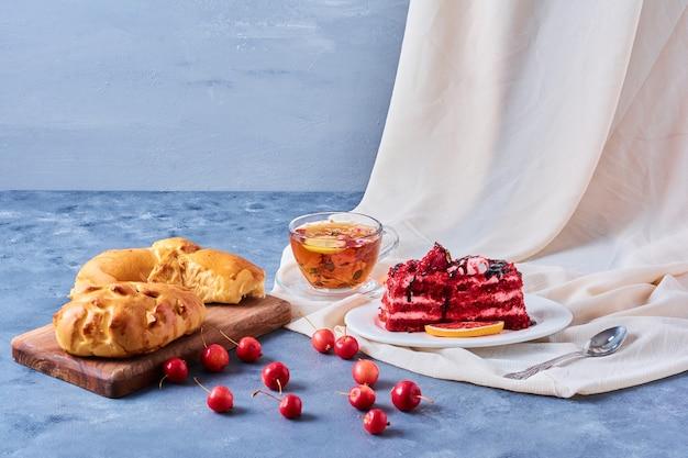 Rood fluweelcake met broodje en thee op een houten raad op blauw Gratis Foto