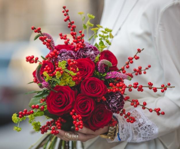 Rood fluwelen boeket van bessen, bloesems en bloemen in de handen van een dame in witte blouse Gratis Foto