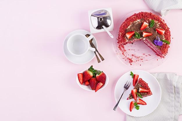 Rood fluwelen cake op een roze tafel. thee drinken. tafel opstelling. bovenaanzicht Gratis Foto