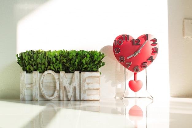 Rood gevormd hart van decoratieve klok en thuis alfabetalfabet Premium Foto