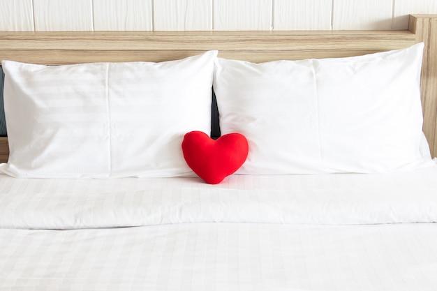 Rood hart en het witte hoofdkussen van het paar op het bed voor liefde, huwelijk en het concept van de valentijnskaart Premium Foto