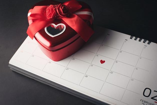 Rood hart in 14 februari op de kalender met hartvormige geschenkdoos, valentijnsdag concept. Gratis Foto