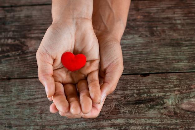 Rood hart in vrouwelijke hand op houten achtergrond. Premium Foto