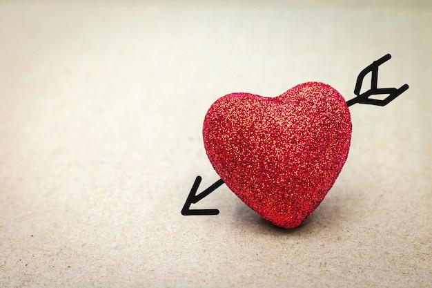 Rood hart met cupidpijl op kartonachtergrond. valentijn concept. Premium Foto