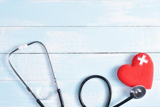 Rood hart met stethoscoop op blauwe en witte pastel houten achtergrond. Premium Foto