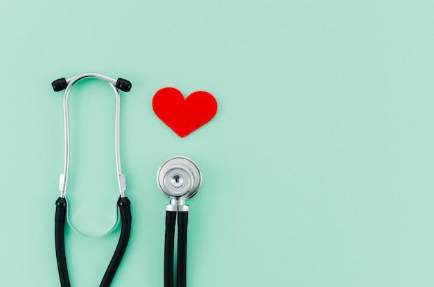 Rood hart met stethoscoop op munt groene achtergrond Gratis Foto