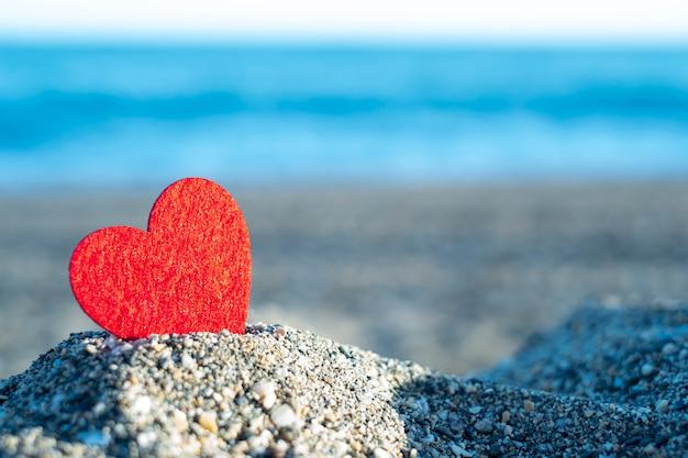 Rood hart op een berg zand aan zee. concept van san valentine Premium Foto