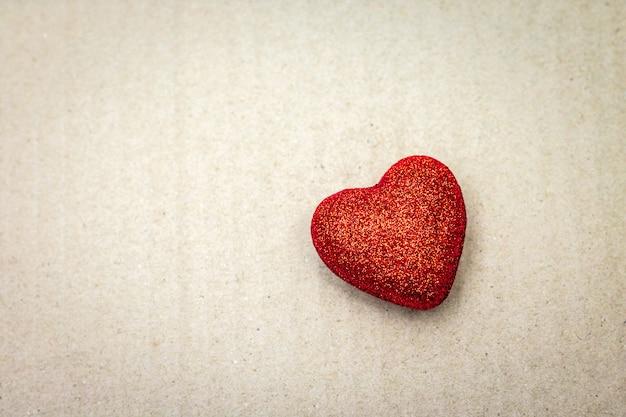 Rood hart op kartonnen achtergrond. valentijn behang. Premium Foto