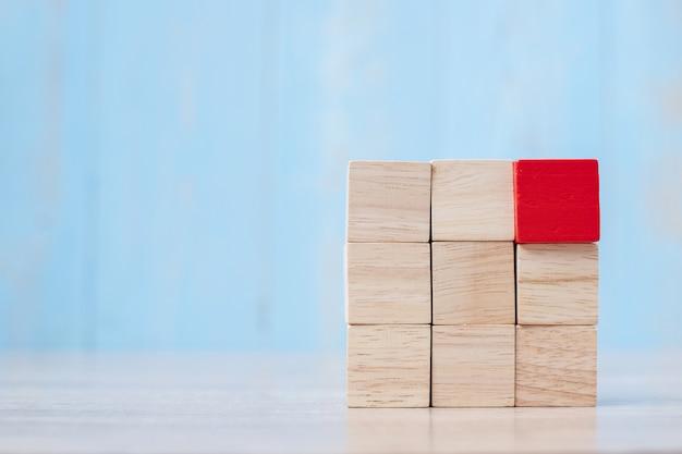 Rood houten blok op het gebouw. bedrijfsplanning, risicobeheer, oplossing, strategie, anders en uniek Premium Foto