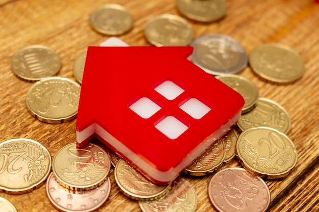 Rood huishuis op de muntstukken van het pakonroerende goederen van de achtergrond dollarstapel het bezit van het de uitgavenbezit het exemplaar ruimte dichte omhoog selectieve nadruk als achtergrond Premium Foto