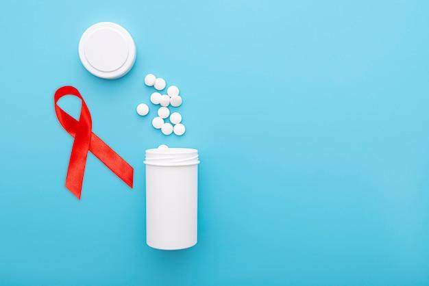 Rood lint, witte pillen en fles op blauwe achtergrond, conceptenbeeld over hiv en aids in de wereld, ruimte voor tekst, hoogste mening Premium Foto