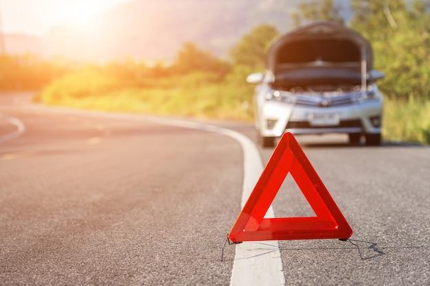 Rood noodsituatieteken en gebroken auto op de weg Premium Foto