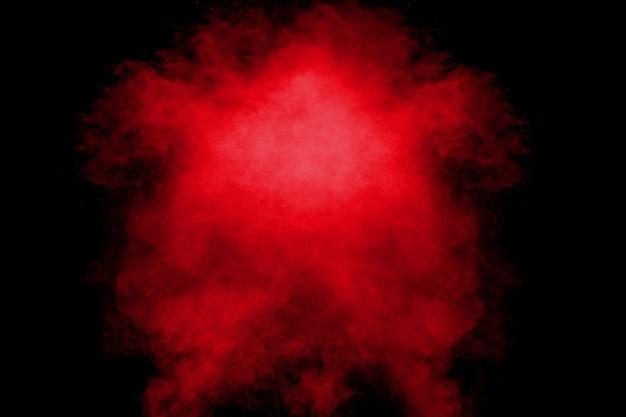 Rood oranje kleur poeder explosie wolk op zwarte achtergrond. Premium Foto