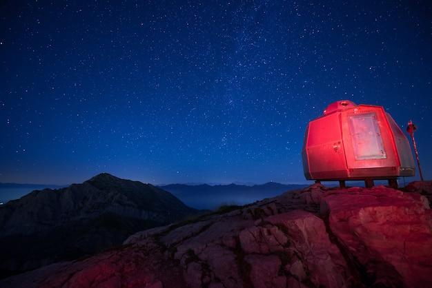 Rood verlicht bivak in de hoge bergen onder een prachtige sterrenhemel Gratis Foto