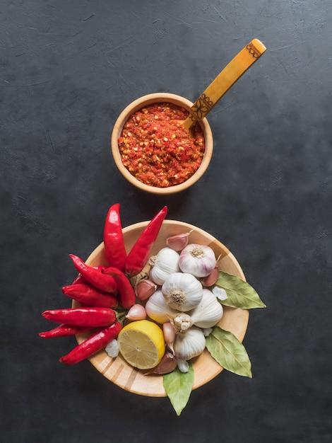 Roodgloeiende saus, knoflook, rode peper en kruiden op een zwarte tafel. bovenaanzicht Premium Foto