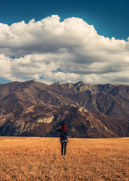 Roodharig meisje in de gouden velden met de rotsachtige bergen op de achtergrond Gratis Foto