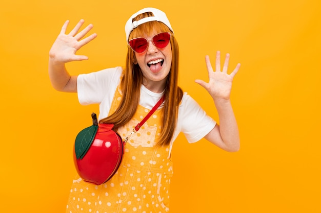 Roodharig meisje in glazen met een rode handtas in de vorm van een appel grimassen naar de camera op een gele bannerachtergrond Premium Foto