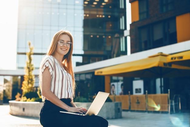 Roodharig meisje met sproeten die door een bril kijken, zit in een bankje voor het bouwen en met behulp van een laptop Premium Foto