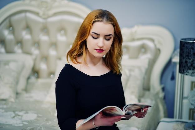 Roodharig meisje op zwarte kledingszitting op bed en het lezen van modetijdschrift Premium Foto