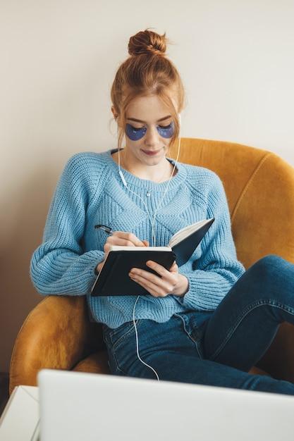 Roodharige dame met sproeten die hydrogel-oogpaden dragen terwijl ze naar muziek luistert en een boek leest op de fauteuil Premium Foto
