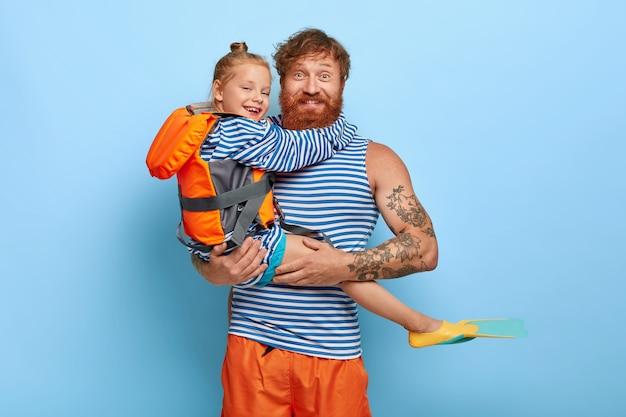 Roodharige dochter en vader poseren samen met zwemspullen Gratis Foto