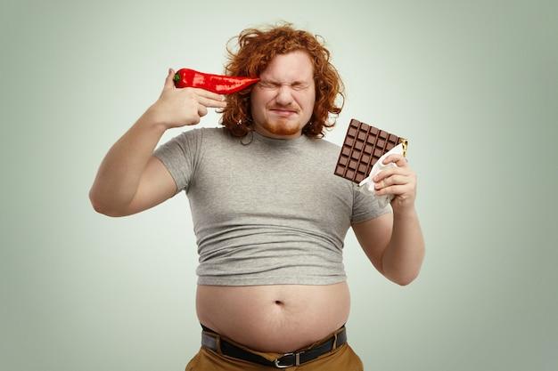 Roodharige jonge europese bebaarde man met gekrompen t-shirt met zijn buik uit spijkerbroek, reep chocola in één hand en rode peper bij zijn slaap, beu met plantaardig dieet Gratis Foto