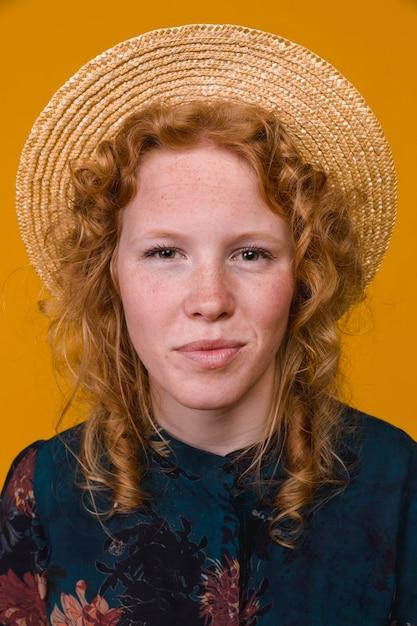 Roodharige jonge vrouw die en camera glimlacht bekijkt Gratis Foto