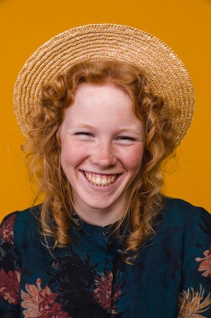Roodharige jonge vrouw die en camera lacht bekijkt Gratis Foto