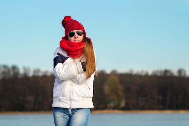 Roodharige mager meisje in vlieger zonnebril, rode pet, rode sjaal en witte winterjas bevriest in de winter Premium Foto